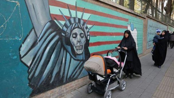 Una mujer iraní camina junto a un grafiti de referencia en la antigua embajada de Estados Unidos en Irán. / AFP. (www.paginasiete.bo)