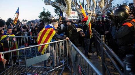 Mozos de Escuadra e independentistas frente al Parlamento catalán. (EFE)
